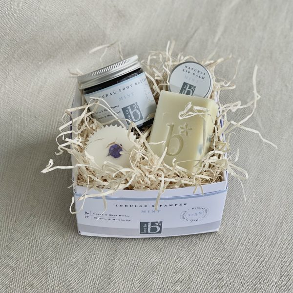 Natural mint pamper box including a mint foot butter, mint lip balm, mint bath melt and mint soap all nestled in a white cardboard box with wood wool on a linen background