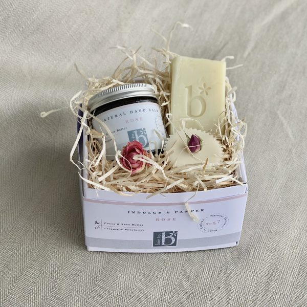 Natural rose pamper box including a rose hand balm, rose bath melt and rose soap all nestled in wood wool and packed into a white cardboard box on a linen background