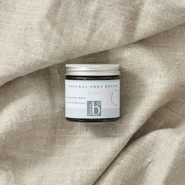 Natural Mint foot butter in an amber glass jar with silver metal lid laid on a brown material
