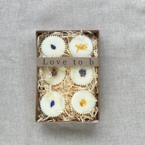 Box of 6 botanical bath melts in a brown cardboard box with a clear lid and sat in wood wool with a brown material background