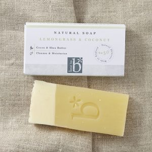 Creamy yellow natural lemongrass and coconut soap below its white rectangular box with a brown material background