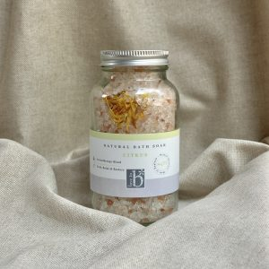 A glass bottle of natural citrus bath salts with aluminium screw lid and white label stood on linen cloth