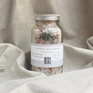 A glass bottle of natural lavender bath salts with aluminium screw lid and white label stood on linen cloth