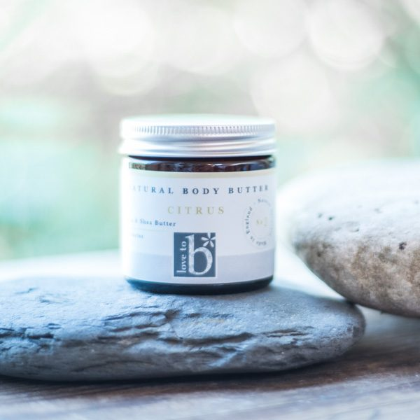 Natural citrus body butter in a brown amber jar with silver metal lid stood on a rock