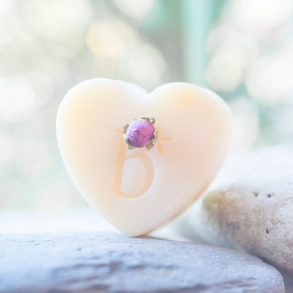 Natural rose heart soap with rose bud balanced on a rock with a green background