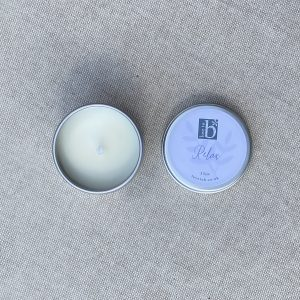 Mini natural soy wax candle relax in a metal tin with lid on a brown material background