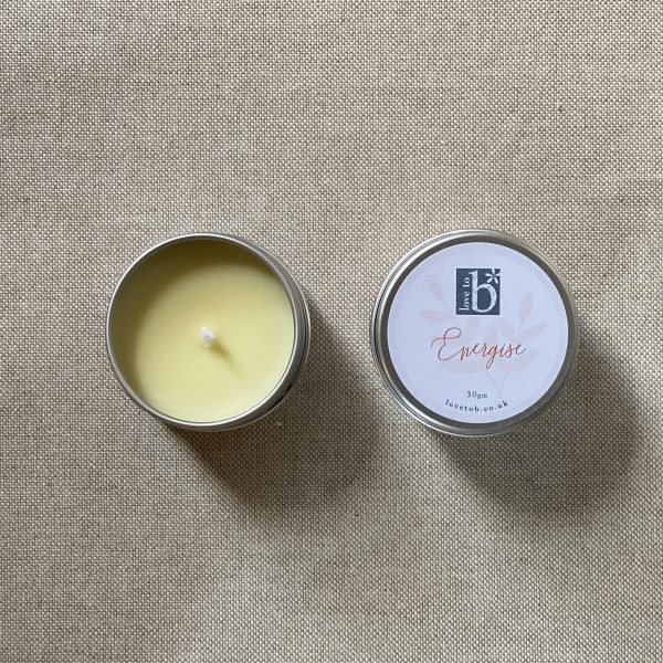 Mini natural soy wax candle energise in a metal tin with lid on a brown material background