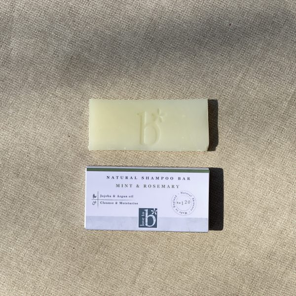 Natural mint and rosemary shampoo guest soap above its white rectangular box with a brown material background