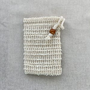 Cream natural sisal soap bag on a brown material background