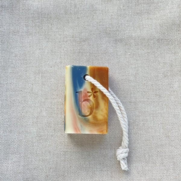 multi coloured 45g bar of tutti frutti natural soap with a rope to hang it with on a linen background