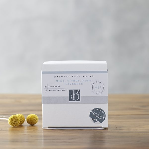 White square natural bath melts box with a grey background on a wooden surface