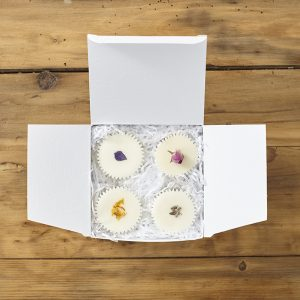 An open white box of natural bath melts with botanicals on them (Mint, citrus, lavender and rose) sat on a wooden surface