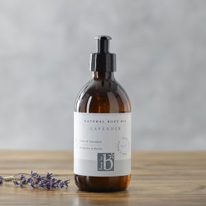 Natural lavender body oil in an amber glass bottle with a white label stood next to some lavender on a wooden surface