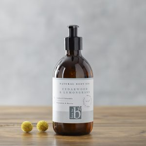 Natural cedarwood and lemongrass body oil in an amber glass bottle on a wooden surface with a grey background