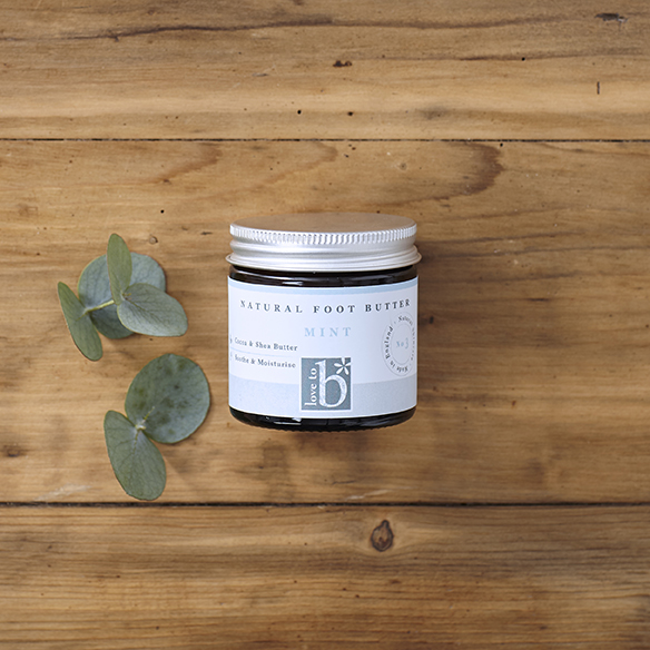 Natural mint foot butter in an amber glass jar with a silver metal lid laid next to some eucalyptus leaves with a wood background