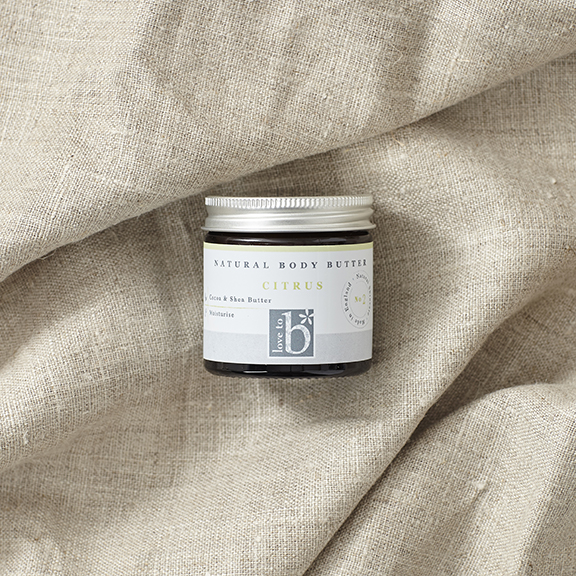 Natural citrus body butter in brown amber glass jar with silver lid laid on a brown material