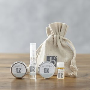 Natural skincare starter kit linen bag behind trial sized cleanser, toner, moisturiser and serum on a wooden surface