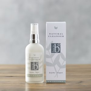 Natural facial cleanser in frosted glass bottle next to its white rectangular box on a wood surface