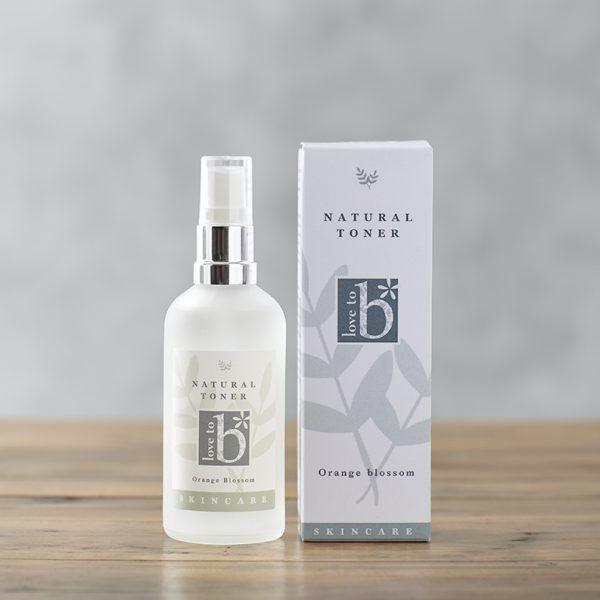 Natural floral toner in a frosted glass bottle next to its white rectangular box on a wooden surface