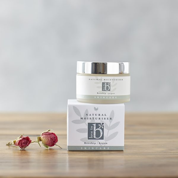 Natural facial moisturiser in a frosted glass jar with silver lid balanced on its white square box next to some rose buds