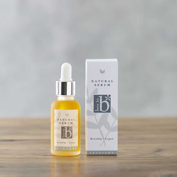 Natural facial serum in a a frosted glass bottle next to its white rectangular box on a wooden surface