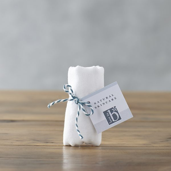 White rolled up muslin cleansing cloth on a wooden surface