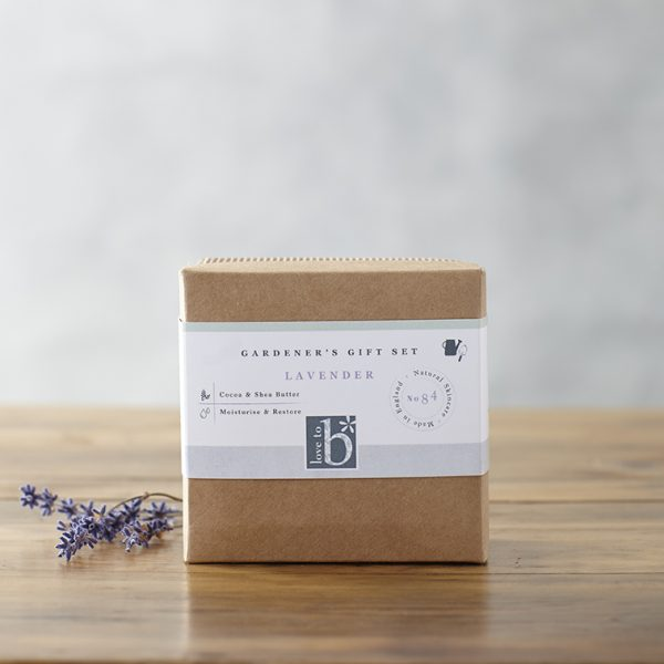 Natural gardener's gift set in a brown cardboard box next to some lavender sprigs on a brown wooden surface with a grey background