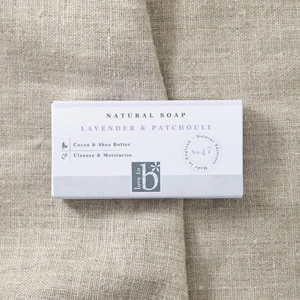 Natural lavender and patchouli soap (guest size) in its white rectangular box on a background of brown material