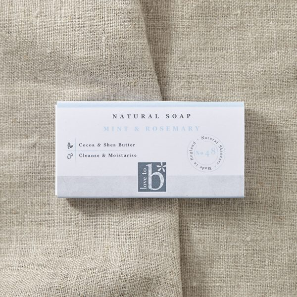 Natural mint and rosemary soap (guest size) in its white rectangular box with a brown material background