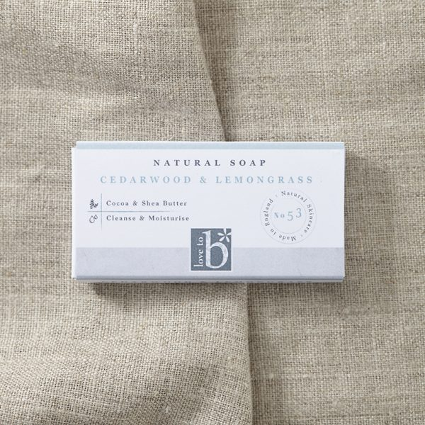 Natural cedarwood and lemongrass soap in a white rectangular box on a background of brown material (guest size)