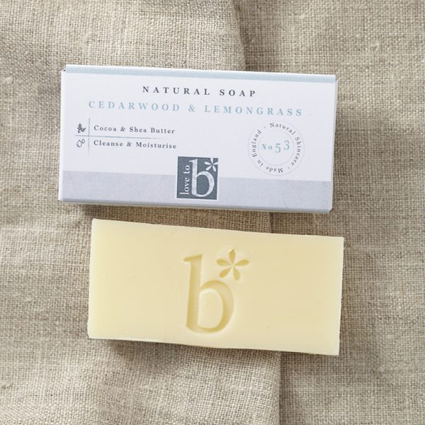 Creamy yellow natural cedarwood and lemongrass soap below its white rectangular box on a background of brown material