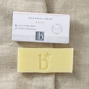 Cream natural rose soap below its white rectangular box with a brown material background (guest)