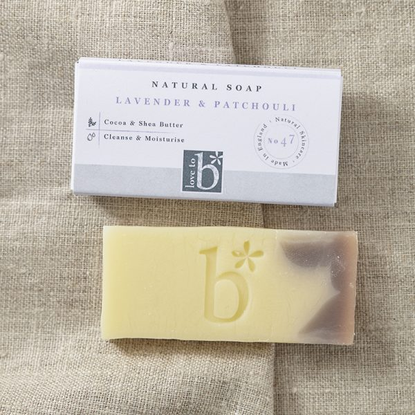 Natural lavender and patchouli soap (guest size) below its rectangular white box on a background of brown material