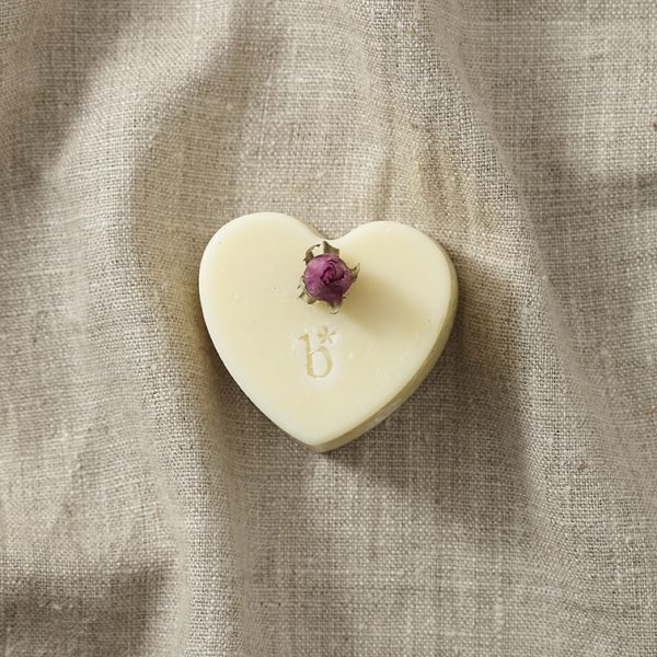 Cream heart shaped natural rose soap topped with a rose bud on a brown material background