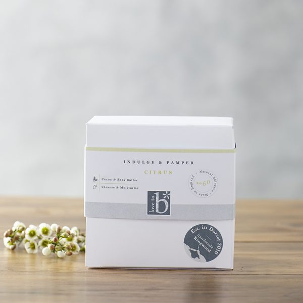 Natural citrus pamper and indulge gift box in a white square box stood on a wooden surface with a grey background
