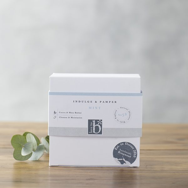 Natural mint pamper and indulge gift box in a white square box stood on a wooden surface with a grey background