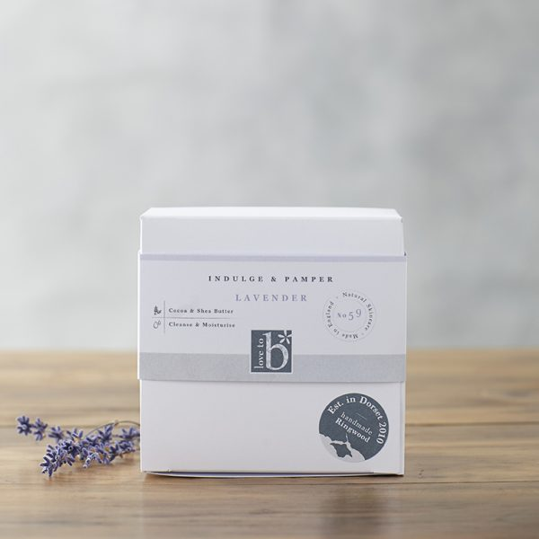 Natural lavender pamper and indulge gift box in a white square box stood on a wooden surface with a grey background