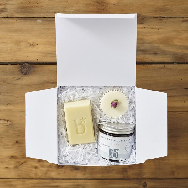 White Natural rose indulge and pamper gift box on a wooden background