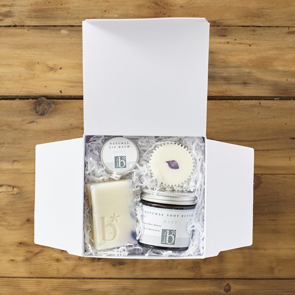 White Natural mint indulge and pamper gift box on a wooden background