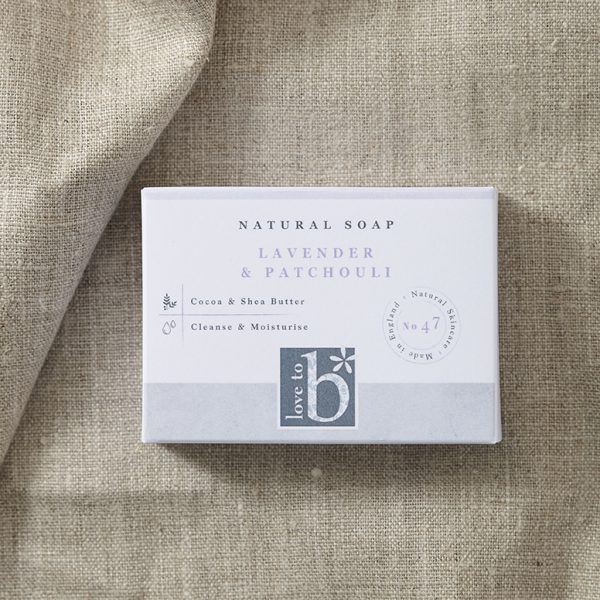 Natural lavender and patchouli soap in its white rectangular box on a background of brown material