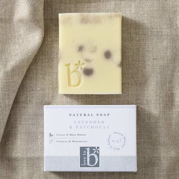 Lilac and cream natural lavender and patchouli soap above its white rectangular box on a background of brown material