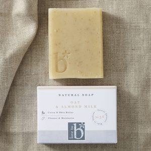 Brown speckled natural oat and almond milk soap above its white rectangular box on a brown material background