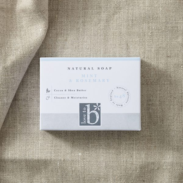 Natural mint and rosemary soap in its white rectangular box on a background of brown material