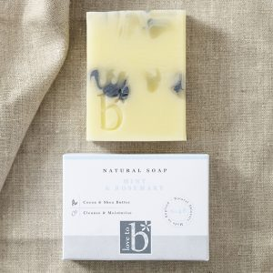 Natural mint and rosemary soap with blue and green swirls above its white rectangular box on a brown material background
