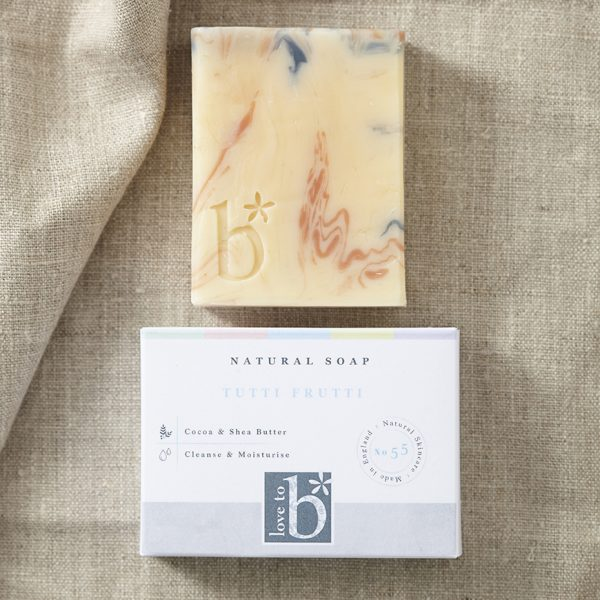 Multi-coloured natural tutti frutti soap above its white rectangular box with a background of brown material
