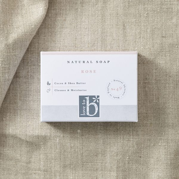 Natural rose soap in its white rectangular box with a brown material background