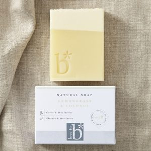 Cream coconut topped natural lemongrass soap above its white rectangular box with a brown material background