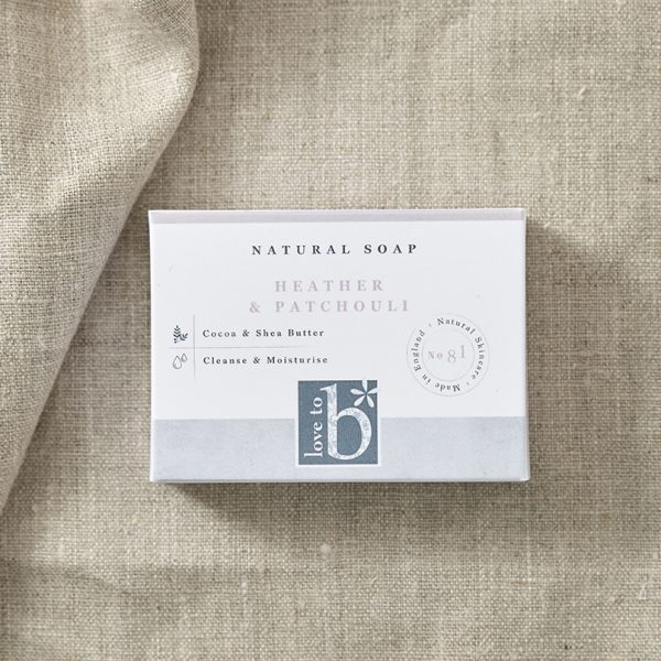Natural heather and patchouli soap in its white rectangular box with a background of brown material