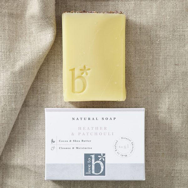 Creamy yellow natural heather and patchoulisoap topped with dried heather above its white rectangular box on a brown material background
