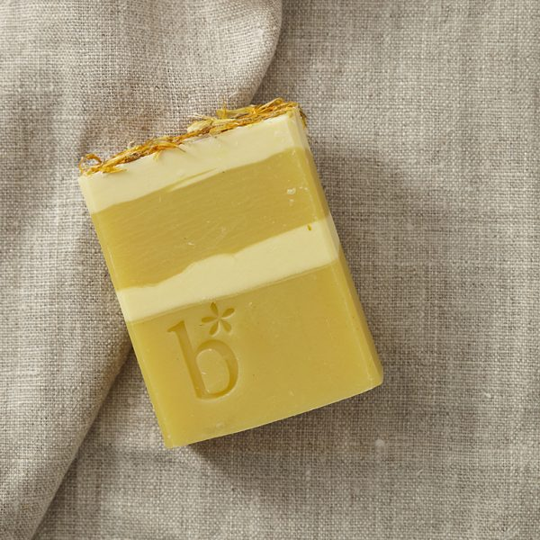 Natural orange bergamot and cinnamon soap coloured yellow and cream on a brown material background